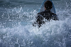 Surf's up. A surfer heading out through a breaker royalty free stock photo