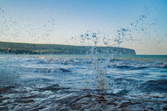 A close up of the waves splashing against the seaside town rocks Stock Photo