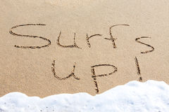 Surf's up - written in the sand Stock Photo