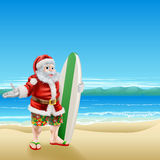 Surf Santa on the beach. Summer Santa in beach wear, long board shorts or Bermuda shorts and flip-flop sandals, holding a surfboard on a sunny beach Royalty Free Stock Photo