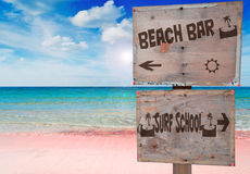 Surf and bar. Surf school and beach bar sign in a beautiful pink beach under a dramatic sky with sun reflection Royalty Free Stock Photos