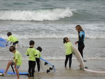 Surf school with children and teachers on the beach. They are on the sand on the shore with the sea and waves in the background Stock Photos
