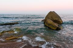 Ocean shore. Big boulder in sea. Waves on sea Stock Images