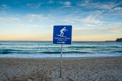 Sunset beach with surf sign. Royalty Free Stock Image