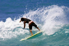 Surf Slashing Surfer. A surfer slashing a wave while surfing in Hawaii Royalty Free Stock Photos