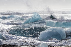 Surf Smashes Blue Ice Royalty Free Stock Images