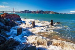 Surf splashes over rocks with the view of Golden Gate Bridge Royalty Free Stock Photo