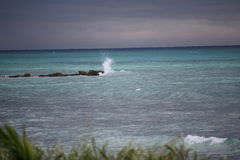 Surf splashing on rocks Jamaican beach Royalty Free Stock Photography