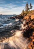 Surf on stony coast of lake with waves under sunrise light at mo Stock Photo