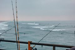 Fishing poles hang over the rail of a pier and over the water. royalty free stock image