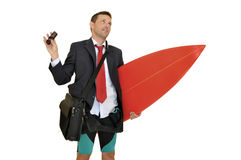 Surf time. Young businessman with surf board recieving a call from the office Royalty Free Stock Images