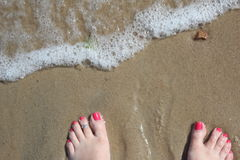 Surf and toes. Toes in sand with surf fast approaching Stock Image