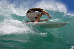 Surf tube ride. A surfer tucking in for a tube ride stock images