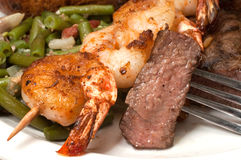 Surf and Turf. Closeup of sirloin steak on fork with shrimp on skewer and green beans Stock Image