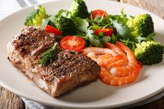 Surf and Turf. Beef steak with royal prawns and fresh vegetables. Close-up on a plate on a table. Horizontal Stock Photos