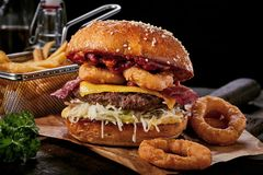 Surf and turf seafood and meat burger. With fried squid rings, melted cheese, crispy bacon and a beef patty served on a wooden board with side potato chips Stock Image