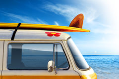 Surf Van. Detail of a vintage van in the beach, with a surfboard on the roof Stock Image