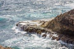 Surf Washing Over Black Stone Royalty Free Stock Image