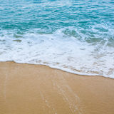 Surf wave is covering a sea beach sand Royalty Free Stock Photos