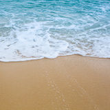 Surf wave is covering a sea beach sand Royalty Free Stock Images
