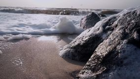 Surf waves with foam approaching a camera near a black stone stock video footage