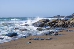 Surf and waves on a rocky coast. With grey overcast skies Stock Photo