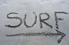 Surf this way. I picture of the word surf and an arrow drawn in the sand Royalty Free Stock Photo