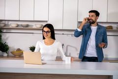 Positive woman using her laptop in the kitchen stock images