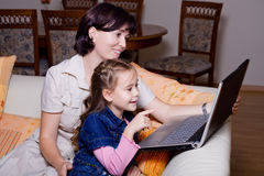 Surfa internet för dotter och för mom Arkivbild