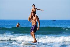 Surfa med ungar - glad ritt för skuldra Royaltyfria Bilder