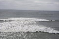 Surfa på en mulen dag på stranden Royaltyfri Foto
