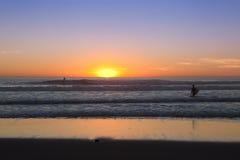 Surfa på solnedgång Fotografering för Bildbyråer