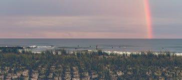 Surfa under en regnbåge på skymning royaltyfria bilder