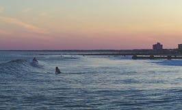 Surfa vid solnedgång Arkivfoton