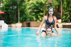 On the surface. Girl sitting on her boyfriend�s shoulders in a swimming pool Stock Image