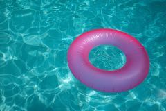 Surface of blue swimming pool with pink buoy inflate stock photos