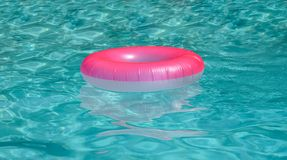 Surface of blue swimming pool with pink buoy inflate royalty free stock photography