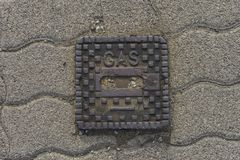 Surface box on street saying `gas`. Surface box on street made of metal saying `gas Royalty Free Stock Photography
