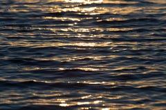 Surface brillante de l'eau de coucher du soleil de couleur chaude sans couture de texture Photos stock