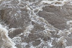 Surface of bubbling brown and dirty water. Royalty Free Stock Images
