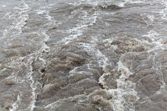 Surface of bubbling brown and dirty water. Royalty Free Stock Image