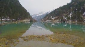 Surface calme de lac de montagne, réflexion dans l'eau, ressort dans les Alpes autrichiens banque de vidéos
