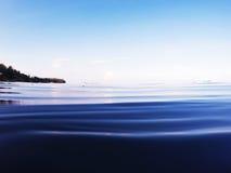 Surface d'eau de mer avec l'eau ondulée et le rivage éloigné La nature tropicale après coucher du soleil a modifié la tonalité la Photographie stock libre de droits