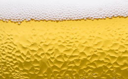 Surface d'un verre de bière avec la mousse et les baisses Image stock