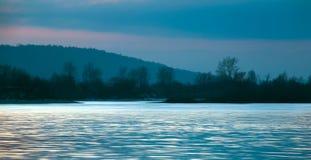 Surface de clignotement de la rivière au coucher du soleil pendant l'hiver tôt image stock