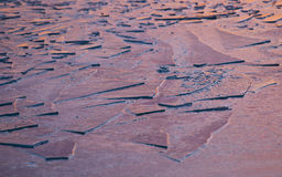 Surface de glace sur un lac au coucher du soleil photos stock