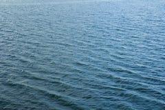 Surface de l'eau avec des ondulations et des réflexions de rayons de soleil Photographie stock libre de droits