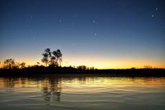 Surface de lac après coucher du soleil avec des étoiles image stock