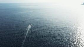 Surface de ondulation de l'eau de mer bleue profonde reflétant la lumière du soleil avec le bateau banque de vidéos