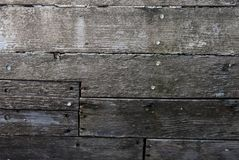 Surface of decaying planks on wooden boat hull. Detail of wooden boat hull eroded by salt and sun; aged wooden planks nailed together Royalty Free Stock Image